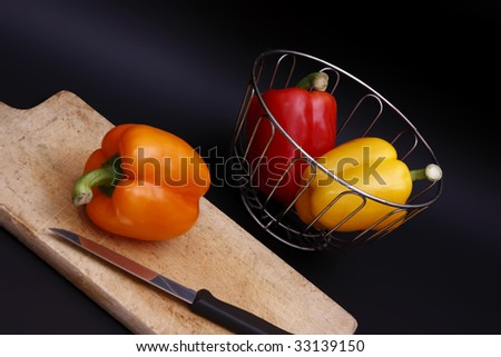 bell peppers in chrome basket and on chopping board