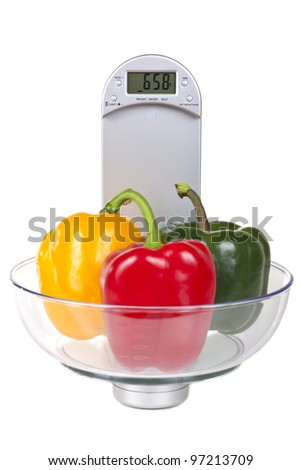 Bell peppers on a electronic kitchen scale, isolated on white background