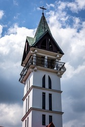 Bell tower (belfry) with cross of catholic church dedicated to Saint Maximilian Maria Kolbe in Cisiec, Silesian Voivodeship, Poland, blue sky background.