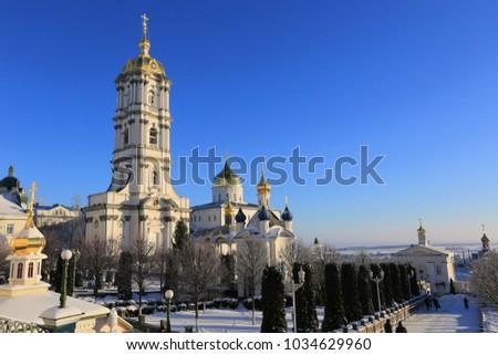 bell tower of the Holy Dormition Pochayiv Lavra in the morning sunlight, Ukraine #1034629960
