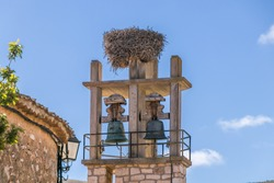 Bell tower with stork nest with a blue sky as background