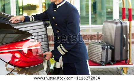 Bellboy taking baggage of guest from thee car to his room