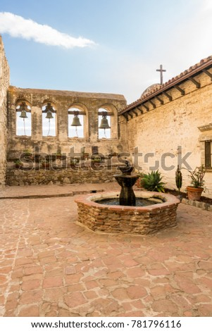 Bells in bell tower surround paved patio at San Juan Capistrano mission