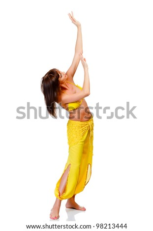 Belly dancer in yellow costume posing against white background
