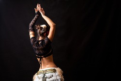 Belly dancer on her back with arms up, in a black background.