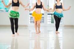 Belly dancers shaking their hips while performing in the dance hall