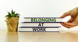 Belonging at work symbol. Books with words 'Belonging at work' on beautiful white background. Businessman hand. Business, belonging at work concept. Copy space.