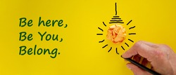 Belonging symbol. Businessman writing words 'be here, be you, belong', isolated on yellow background. Light bulb icon. Business, belonging and better inclusion, belong here concept. Copy space.
