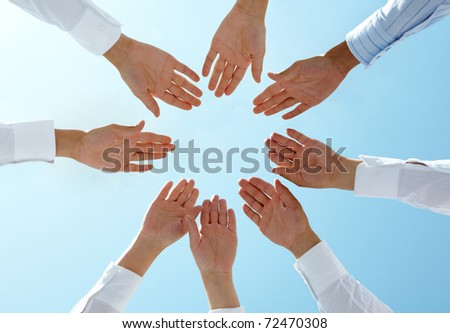 Below angle of circle of people hands with blue sky above