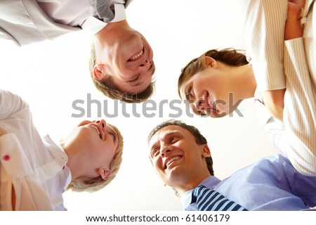 Below angle of happy business people looking at each other