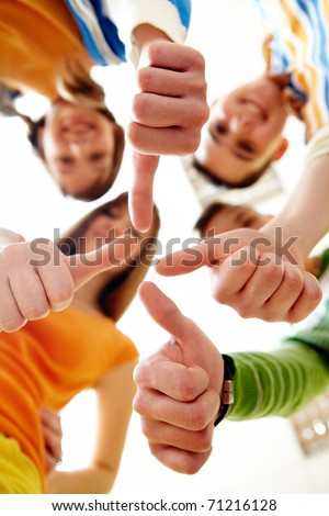 Below angle of happy teens showing thumbs up