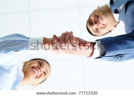 Below angle of successful associates handshaking after striking deal