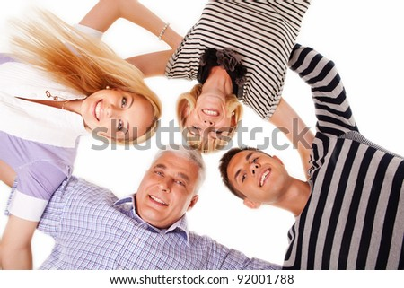 below view of a beautiful family of four standing in a circle and looking at the camera isolated on white - stock photo