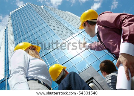 Below view of business partners in helmets looking at modern office building against cloudy sky