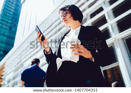 Below view of concentrated woman with coffee to go reading news about finance world on manhattan while standing on city streets during work break, attractive female using 4g connection on cellular