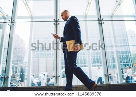 Below view of confident entrepreneur dressed in formal wear typing sms message on smartphone going in office building.Proud ceo installing app on modern telephone using 4G internet