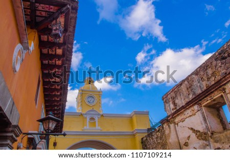 Below view of famous yellow arch with clock, lopcated in the city center of Antigua Guatemala, in a beautiful sunny day and blue sky