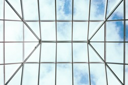 Below view of glass roof consisting of square and triangle segments with sky visible through