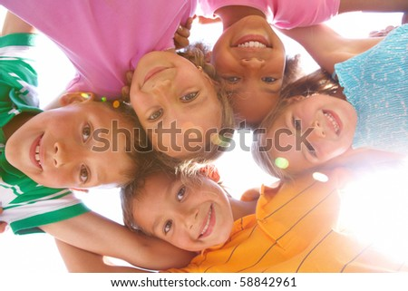 Below view of happy children embracing each other and smiling at camera