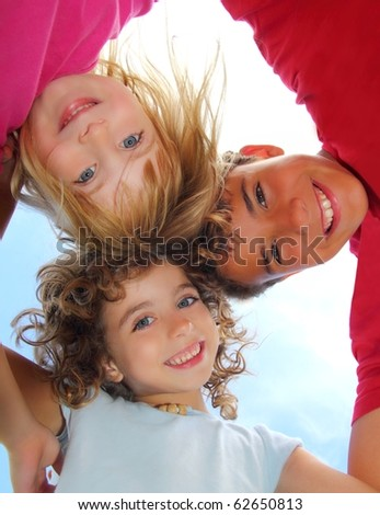 Below view of happy three children embracing hug each other smiling camera