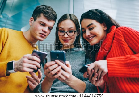 Below view of happy young people in casual wear laughing while watching funny video in blog on smartphone device.Positive friends sharing media on smartphone using bluetooth connection and 4G internet
