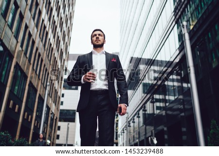 Below view of intelligent male entrepreneur dressed in luxury suit walking near skyscrapers in financial district of megalopolis, serious businessman with takeaway cup going at street downtown #1453239488