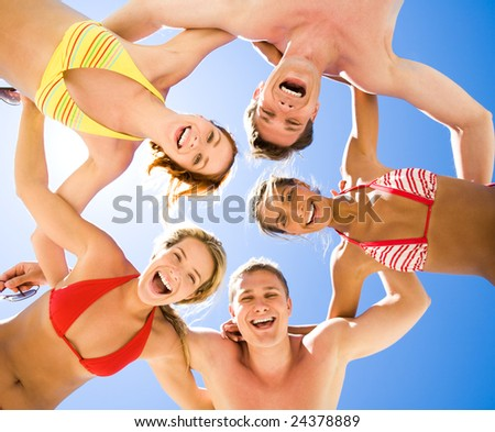 Below view of laughing teens in swimwear looking at camera with blue sky above them