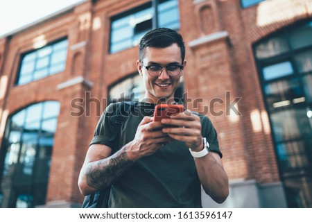 Below view of millennial smiling hipster guy reading message on mobile phone standing outdoors, cheerful man satisfied with 4G internet connection in for online chatting with followers from web page