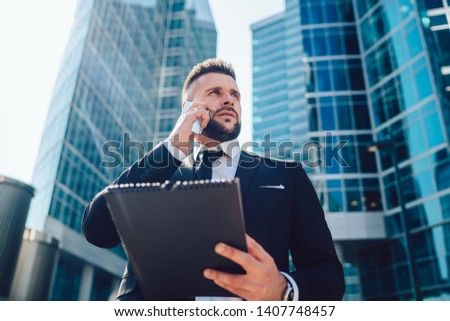 Below view of pensive entrepreneur using cellphone gadget for online consultancy during accounting time in megalopolis street,intelligent man making international cell conversation via app on cellular #1407748457