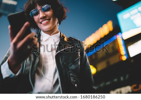 Below view of pretty woman in cool eyeglasses and trendy wear smiling on metropolitan street with night lights enjoying songs from playlist in earphones, girl reading sms with good news on smartphone