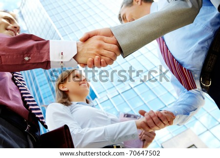 Below view of rows of happy partners handshaking outdoors on background of modern building
