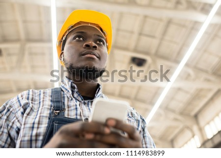 Below view of serious introspective young African construction engineer in yellow hardhat texting message on smartphone and looking into distance at construction site