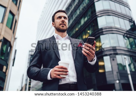 Below view of thoughtful experienced male holding cellphone gadget during coffee break in financial district, pensive man pondering on trade info waiting for online professional consultancy