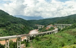 Belt and Road Initiative: Chinese Xiaomo Highway bridge under construction in the green jungle between Lao border town Boten and Mengla, Yunnan, China