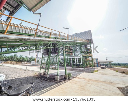 Belt conveyer of feed woof chipper fuel systems to boiler for product steam to steam turbine generator in biomass power plant. #1357661033