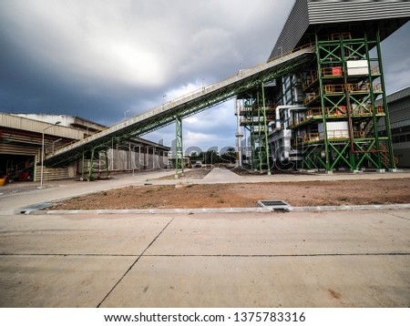 Belt conveyer of feed woof chipper fuel systems to boiler for product steam to steam turbine generator in biomass power plant. #1375783316