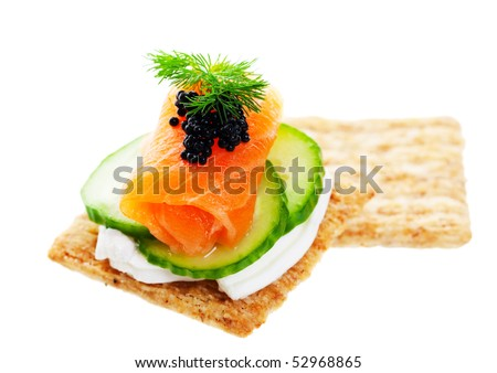 Beluga Caviar on fresh, raw salmon with baby cucumber and goat cheese; garnished with a sprig of fresh dill.