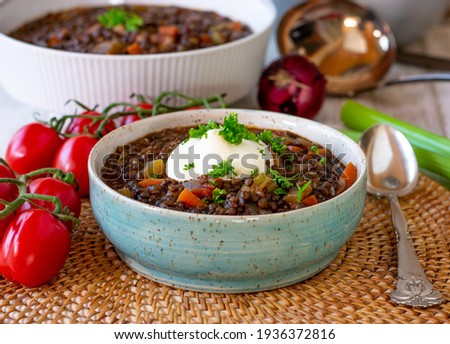 Beluga lentil stew with vegetables and sour cream served in bowl with spoon  Foto stock ©