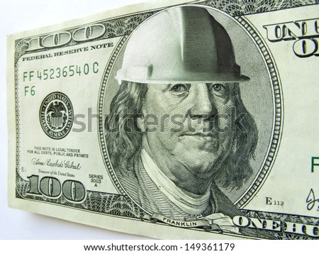 Ben Franklin wears a hard hat on this one hundred dollar bill which might illustrate the cost of construction or safety in a business or industrial environment.