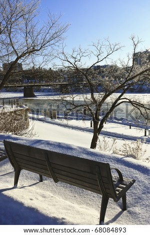 Bench along the icy cold waters of the Saskatchewan River in Saskatoon, Canada