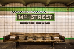 Bench at New York City subway station with vintage tile wall