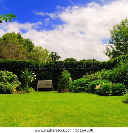 Bench in beautiful green garden under partly cloudy blue summer skies.
