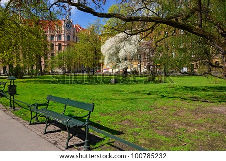 Bench in city park of Krakow in spring time, Poland