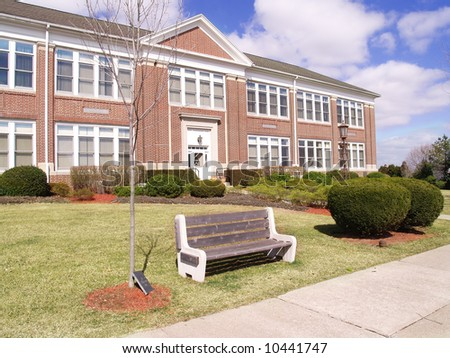 bench in front of a two story red brick building