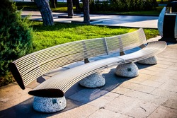 Bench in the shape of a wave. Outdoor bench in local park. Steel material Park steel bench. Garden bench seat. Steel exterior material.