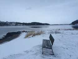 Bench in the snow in winter landscape on the coast of Vestfold, Norway