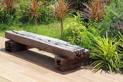 Bench made from an old wooden railway sleeper with a background of a green tropical garden in bright sunshine