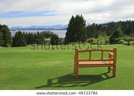 Bench on a green lawn and mountain landscape around Bariloche, Argentina