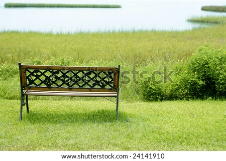 Bench over the green grass on the lake, peace metaphor