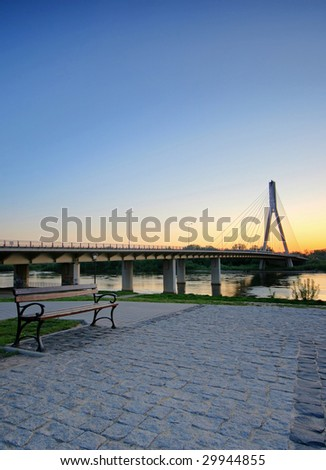 bench over Vistula river at sunrise, near Swietokrzyski bridge, Warsaw, Poland